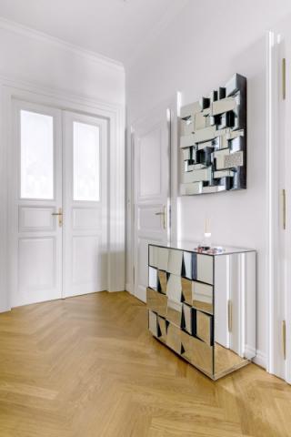 Úzká chodba disponuje velkou šatní skříní amajiteli dodatečně vybaveným zázemím, složeným zkomody azrcadla sdekorativním charakterem