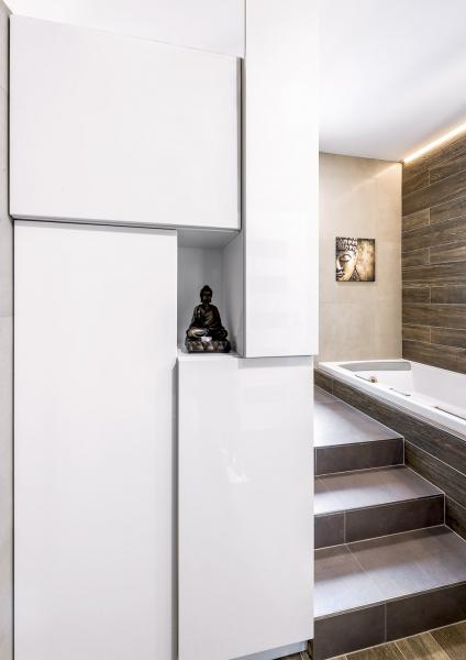 Pohled odtoalety: nazadní stěně sprchového koutu jsou atypicky poskládané úložné skříňky. Dovyšší úrovně se sprchovým koutem ačástečně zapuštěnou vanou vedou schody