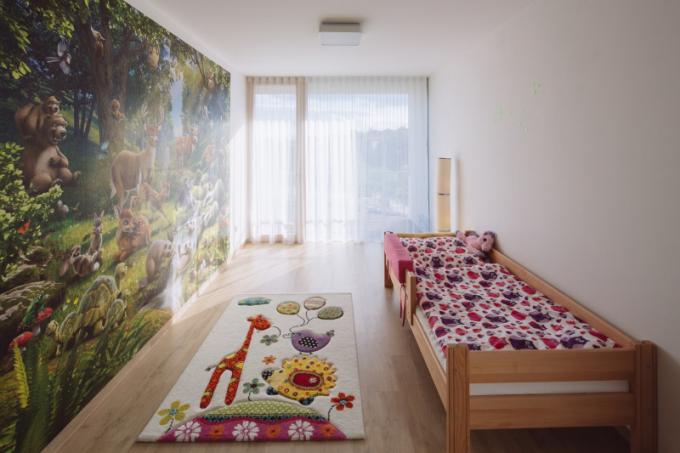 Dlouhá stěna naproti schodišti může sloužit jako domácí galerie, kterou lze posuvnými dveřmi oddělit od privátní části domu se dvěma dětskými pokoji, prostornou koupelnou a šatnou