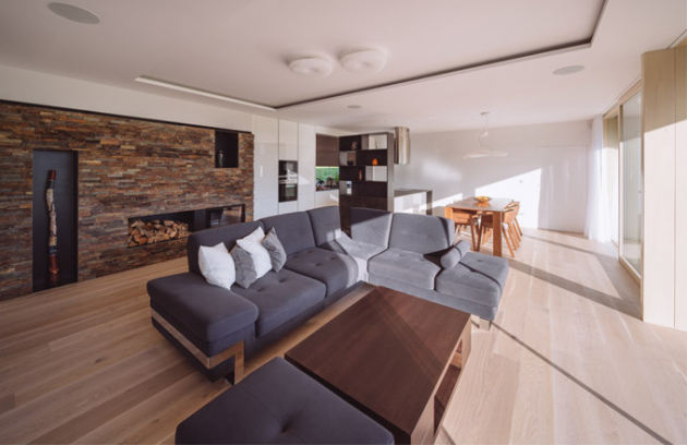 Dominantou velkého obývacího pokoje je krbová stěna obložená štípanou horizontálně kladenou břidlicí.