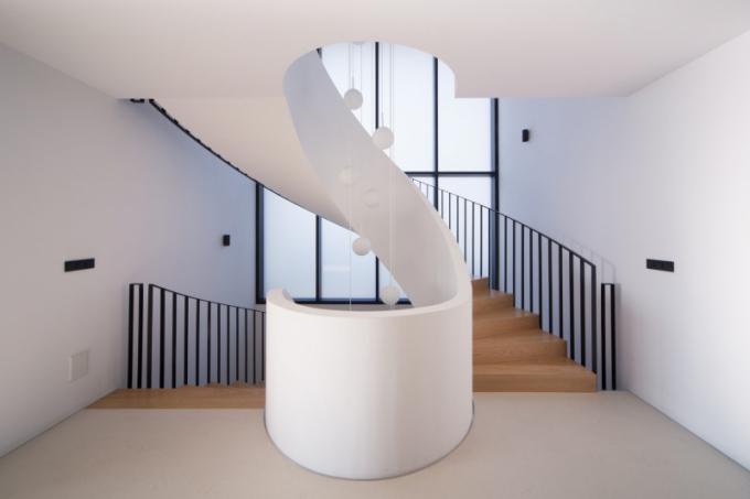 Zásadním prvkem návrhu interiéru domu je schodišťová hala smonolitickým točitým schodištěm, které tvoří vertikální komunikační osu domu a zároveň vnitřek domu prosvětluje díky své západní prosklené stěně.
