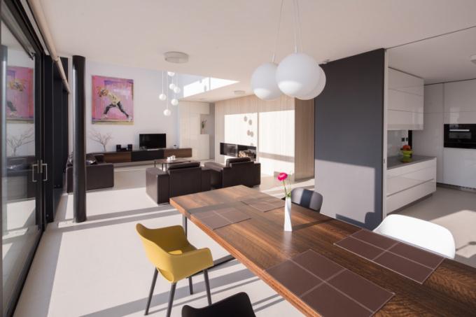 Dalším je pak hlavní obytný prostor. Jeho součástí je jídelna snávazností na kuchyň a převýšený obývací pokoj, kde je umístěn travertinem obložený krb, nad nímž probíhá galerie sknihovnou.