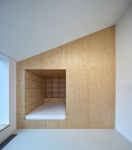 Zatímco interiér počítá svyužitím řemeslných nábytkových prvků, přírodních materiálů ibarev, vnějšímu výrazu domu přispívá určitá střízlivost– absence detailu (střešní plášť bez přesahu, omítka bez soklu, okno bez rámu). Minimalistická forma je vtomto případě odpovědí na všudypřítomnou přesycenost vokolí.