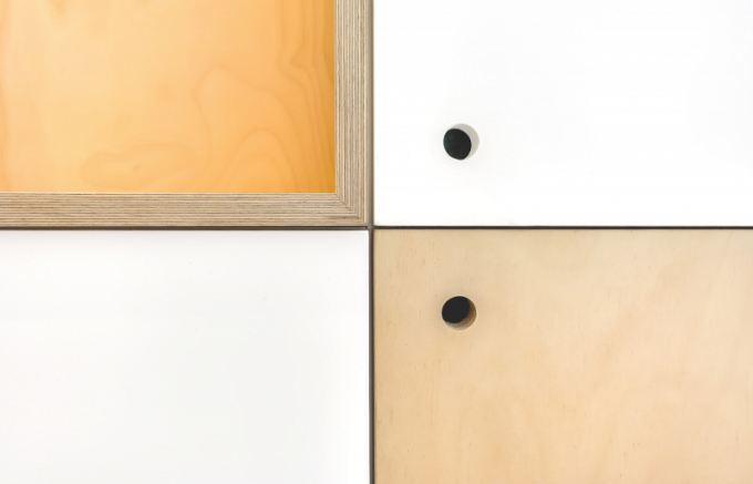 Od vstupu po celé délce bytu vede dlouhá stěna súložným prostorem. Její součástí jsou 4 výklenky a kontrastující přední panely z bílé a březové překližky.