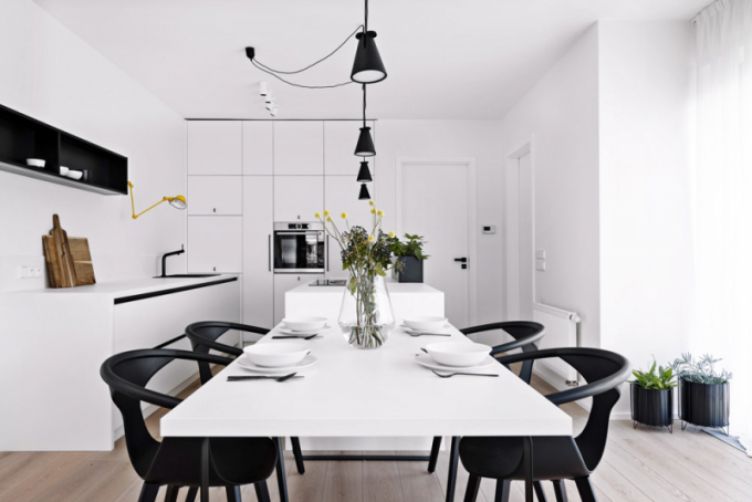 Velká část bílých ploch jsou utajené úložné prostory skryté zadvířka zbílého lamina, ty pak velmi dobře kontrastují sodvážnými černými stěnami, které architekti opatřili výmalbou (Dulux). Kuchyně byla vyrobena namíru odtruhláře, osazena kvalitní varnou deskou sintegrovanou digestoří odznačky Bora