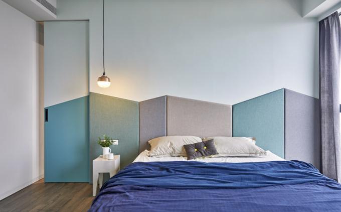 Čalouněné čelo postele složené zpanelů vyrobených namíru ozvláštňuje minimalisticky zařízený prostor ložnice rodičů