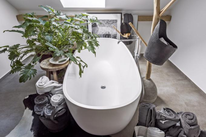 Volně stojící vana je obklopena prvky z masivu, výraznou květinou anádobami zhotovenými ze starých pneumatik