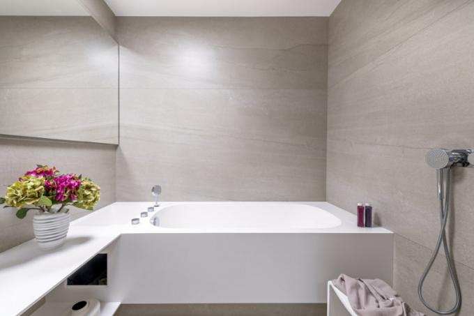 Architekti podsvítili jak odskočený sokl vany ve spodní linii, tak i zrcadlo shora izespod. Vytvořili tak efekt ambientního intimního osvětlení, které současně místnost opticky rozšiřuje