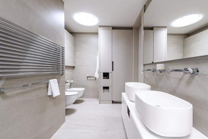 Skříň na pračku s prostory pro ukládání věcí architekti navrhli z lakované MDF v odstínu dlažby tak, aby splynula s okolními stěnami