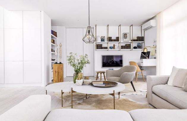Součástí obývacího pokoje je malá pracovna. Vícedílný Ottův naučný slovník je rozmístěn naefektních policích vyrobených zbíle lakované MDF desky alakovaného kovu vbarvě patinované mosazi