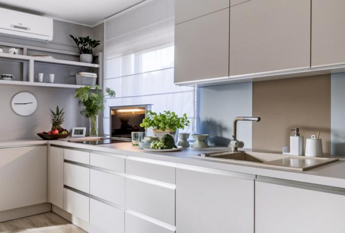 Kuchyň vpudrovém ladění je zhotovená namíru podle návrhu studia Mibiko. Varná deska pod oknem je opatřena výsuvnou digestoří. Obdélníkový stůl zdrásaného běleného dubu zhotovili truhláři namíru. Doplňuje ho šest čalouněných židlí Damian, které zajišťují dostatečný komfort ipři delším stolování