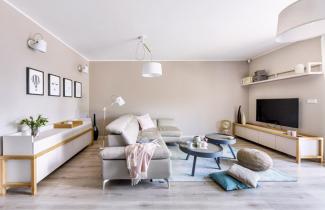 Obývací pokoj je vybaven rohovou koženou sedací soupravou snastavitelnými podhlavníky advěma komodami zhotovenými namíru vdesignu studia Mibiko. Odpočinkovou zónu dotvářejí dva konferenční stolky Careli (Hoorns) sbetonovým dekorem topu. Osvětlení zajišťují svítidla zkolekce Looker (Mantra), stejné značky je istropní svítidlo Nordica
