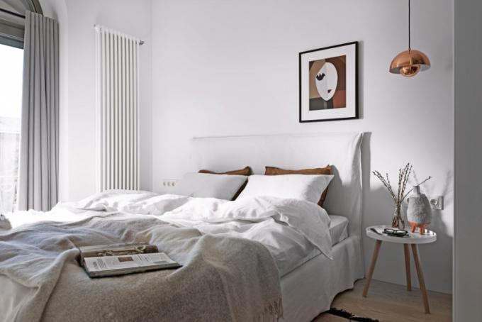 Prostor ložnice zabírá zanedbatelnou část dispozice bytu. Designérka Olha Wood nazákladě tohoto faktoru zvolila řešení pomocí bílé barvy, ato včetně doplňků