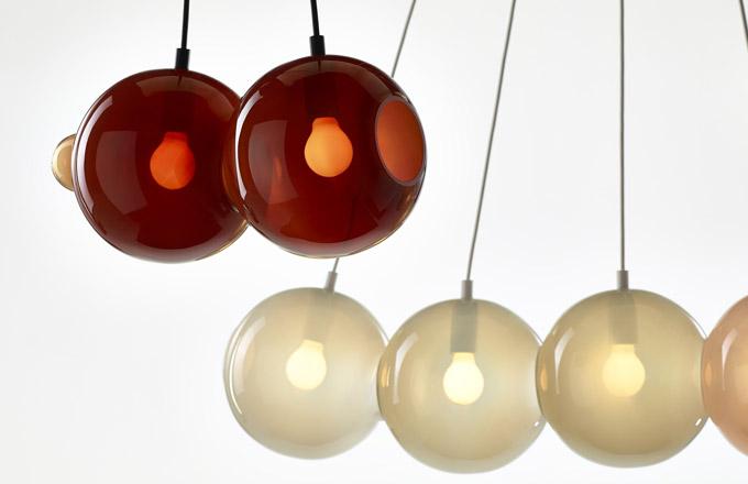 Závěsné svítidlo Pendulum (Bomma) zručně foukaného skla je inspirováno Newtonovou kolébkou demonstrující zachování hybnosti aenergie.