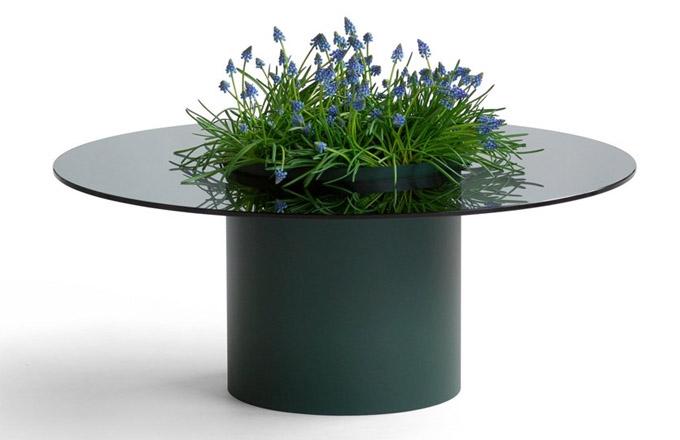 Odkládací stolek Bucket (Blå Station) je vybaven válcem, který proniká skleněnou deskou aokázale vybízí kuložení květin, občerstvení, hraček...