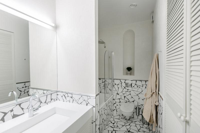 Prostor koupelny byl zmenšen ve prospěch kuchyně, ale rozhodně tím nebyla narušena její funkčnost. Vpravo od vstupu jsou ve skříni ukryty pračka a sušička, kotel a žehlicí prkno.