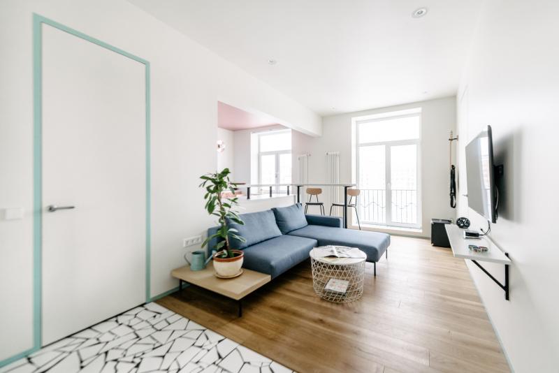 Zařizování obývacího pokoje bylo velmi jednoduché: pohovka, televize a police pod ní. Své místo má i barový pult, který je pokračováním kuchyňského prostoru. Namísto lustrů, které nezapadaly do minimalistického konceptu, designéři zvolili vestavěná světla a lampy.