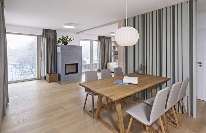 Dominantním prvkem je jídelní stůl, který má roli jakéhosi středu (srdce) interiéru. Autorky najeho výběru nešetřily, vrozpočtu patřil mezi priority. Je zmasivního dubového dřeva odznačky Skanfort asvým zpracováním velmi dobře kontrastuje slakovanou povrchovou úpravou dekorativní japonské stěny. Ta je vyrobena zlepených dřevěných profilů