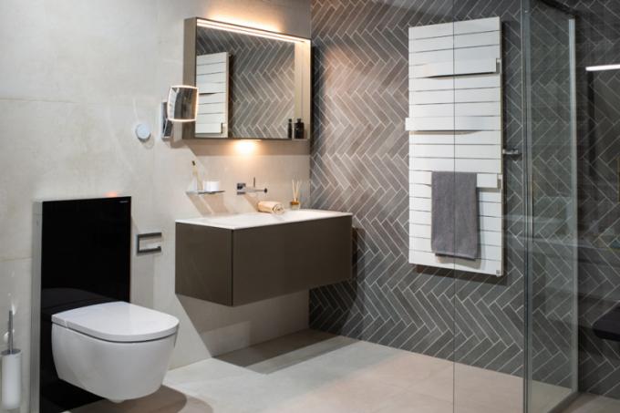 """Elegantní funkčnost Krásná koupelna na první pohled a technologická """"bomba"""" na druhý. Technologie sanitárního modulu Geberit Monolith, který za skleněným designem ukrývá integrované odsávání zápachu a barevné podsvícení. Toaleta Villeroy&Boch s bidetovací sprškou nebo kosmetické zrcátko KEUCO, u něhož si můžete nastavit intenzitu a teplotu osvětlení."""