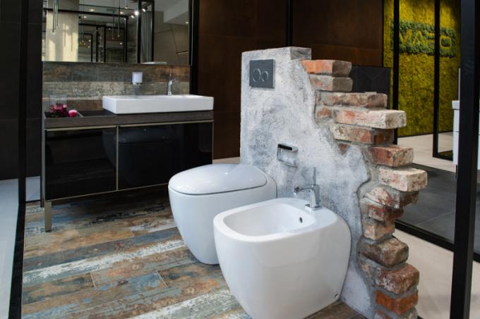 Syrový industriál Design průmyslových továren evokuje koupelna, kde dekor dlažby připomíná oprýskaný lak na dřevěné podlaze, v kombinaci s ostrými hranami plechovkových detailů se skleněným povrchem u podumyvadlové skříňky Geberit, působí velmi industriálně. Vše je zjemněno oblými tvary sanitárních zařizovacích předmětů, které vyvažuje ovládací tlačítko Geberit z pravé břidlice.