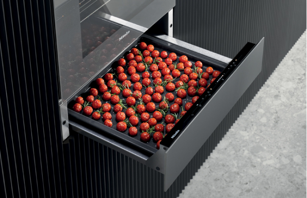 Umí udržet jídlo teplé, lze s ním vařit při nízkých teplotách nebo dokonce sušit ovoce: všestranný 14 cm vysoký gurmánský nahřívač Miele ESW 7010 v grafitově šedé barvě. (Foto: Miele)