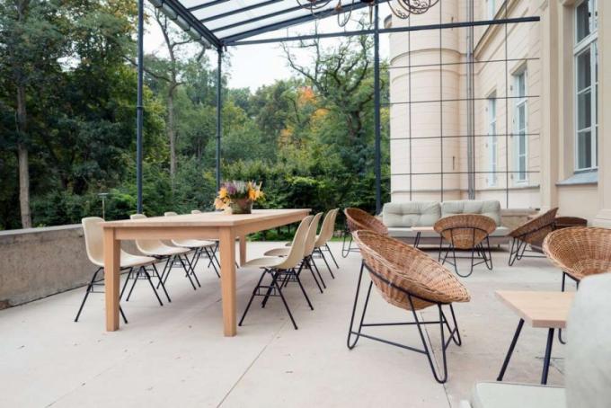 Na terase designéři umístili stoly z vlastní produkce, dále židle Eames z konce 60. let a křesla socelovou konstrukcí ze stejné éry.