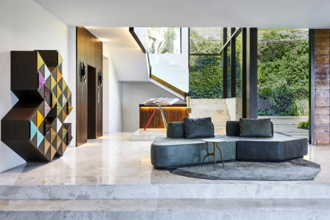 Pestře zbarvená geometrická skříňka Arlequin C (Emmemobili) designéra Ferruccia Lavianiho je doplněna dvoubarevnou semišovou pohovkou, ostře řezaným kobercem a organicky tvarovaným bočním stolem.