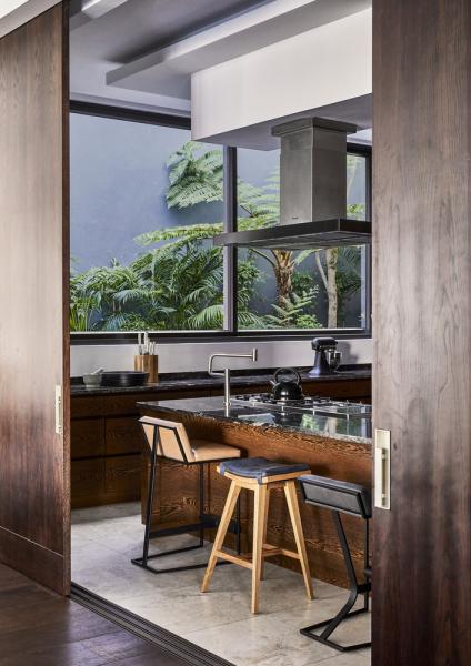 Kuchyň je propojená s jídelním prostorem posuvnými dveřmi. Barový pult se žulovou deskou doplňují barové židle Faye, Frank a Neo značky OKHA.