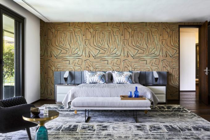 Hlavní pokoj pro hosty je zařízený ve stejném designu jako celý dům. Zajímavým prvkem je tapety Graffito od Kelly Wearstler a koberec vyrobený na zakázku, který prostřednictvím volných linek vytváří nápadité vzory. Geometrické stolní lampy v nerezové oceli (OKHA) elegantně ohraničují postel.