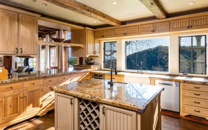 Kuchyň je ve venkovském francouzském stylu sdřevěným nábytkem na míru, mramorovými pracovními plochami a kuchyňským ostrůvkem.