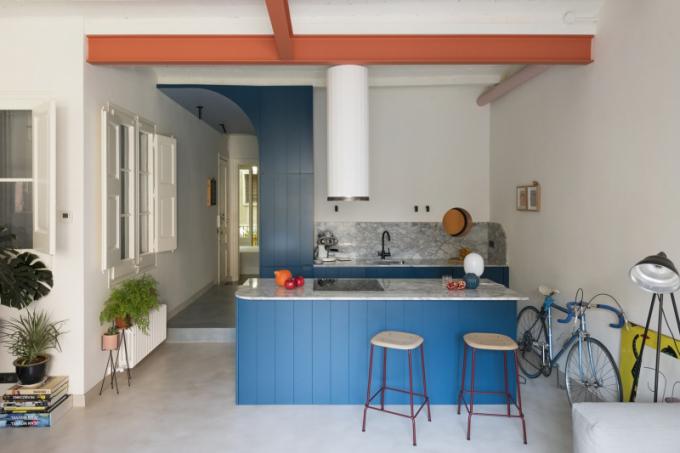 Povrch kuchyňských skříněk a kuchyňského ostrůvku z lakovaných MDF desek s výraznou drážkou je dokonale sladěný s boxem v centru prostoru, ukrývajícím koupelnu a vestavěné skříně