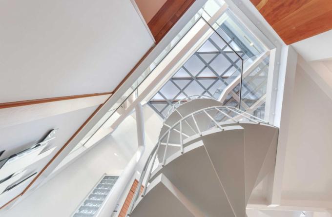 Velká okna včetně střešního nad širokým točitým schodištěm zaplavují interiér slunečním světlem.