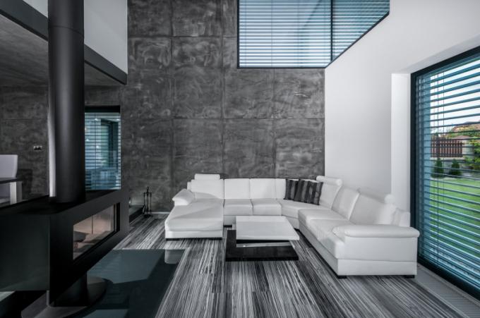 Obývací prostor zčásti vyplňuje bílá sedací souprava a konferenční stolek vyráběný stejně jako veškerý další nábytek na míru.