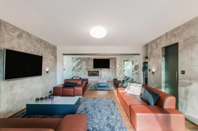 Když smanželkou dispozici domu promýšleli, začali obývacím pokojem a krbem (s důmyslným přikládáním ze zadní technické místnosti). Shodli se, že by měl být takovou dominantou interiéru a místem, kde se budou všichni scházet. Zněj se vstupuje úzkou chodbou do ložnice manželů.