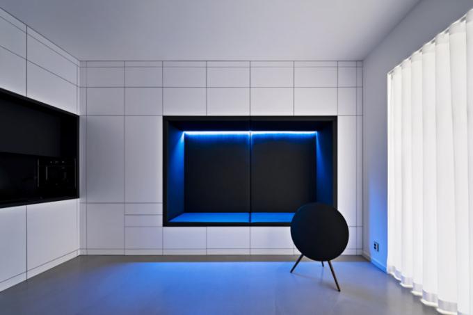 Světlé, hladké plochy maximalizují volný prostor. Prázdné objemy pohovky akuchyně jsou snimi záměrně vkontrastu