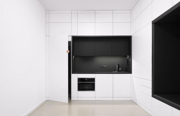 Kompaktní blok obsahuje všechny nezbytné funkce aprvky iplně vybavenou kuchyň. Pootevřené dveře naznačují průchod dál dosoukromé části interiéru