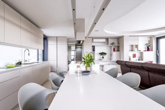 Materiálové propojení napříč prostorem je jedním znosných prvků tohoto interiéru. Vkuchyni je pohledová část linky aostrova vyrobena zbéžové MDF desky, vnitřní korpusy zšedého lamina