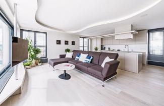 Výrazným prvkem je nepravidelně tvarovaný organický podhled, který prostřednictvím ukryté LED pásky osvětluje celou obývací část spohovkou atelevizí
