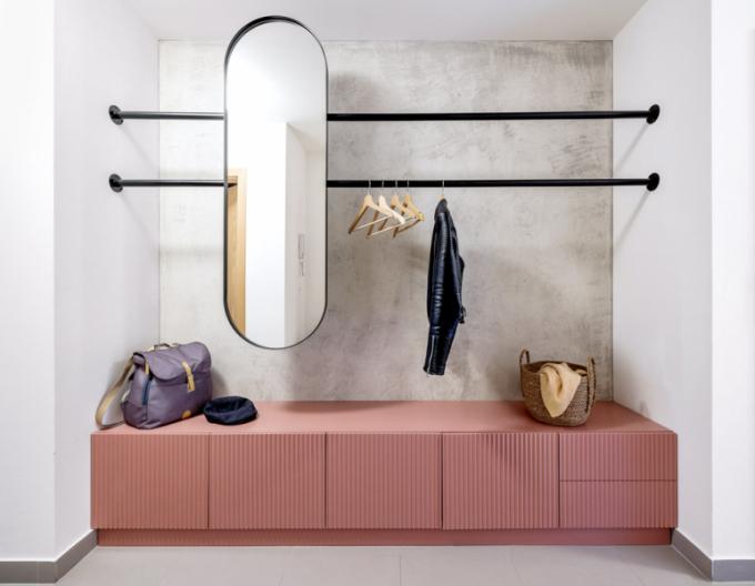 Přestože nika vchodbě vyzývá kběžnému umístění vestavné skříně, architekti se rozhodli pro reprezentativní podobu vstupního prostoru. Zvolili jen botník nasezonní obuv zfrézované alakované MDF desky, tyče svěšáky azrcadlo