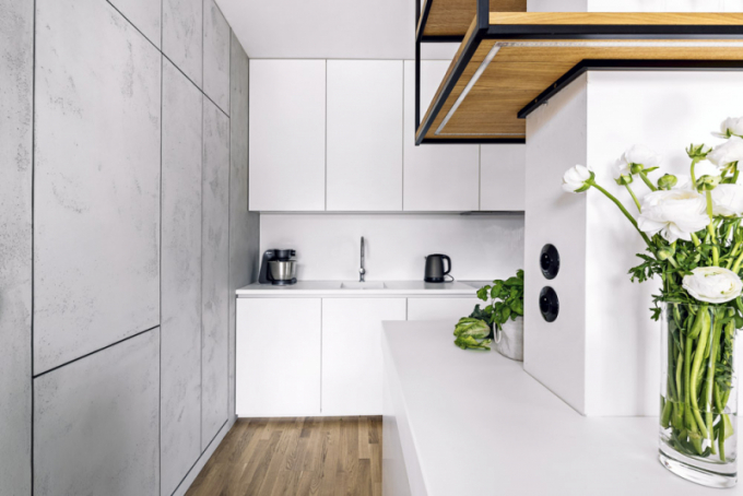 Napřání majitelky má kuchyň bílou barvu. Nábytek je vyroben zlakované MDF desky apracovní deska zcorianu. Všechny nezbytné spotřebiče jsou vestavěné. Stěna pokrytá betonovou stěrkou skrývá chladničku apotravinovou skříň. Díky použití otevírání napřítlakový systém nebyly použity úchytky, azůstal tak zachovaný opticky celistvý výraz stěny
