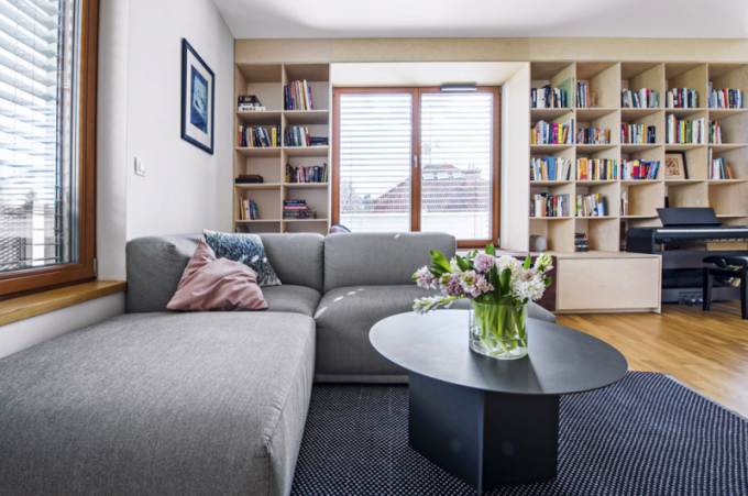Čalouněná sedací souprava (Muuto) je doplněna konferenčním apřídavným stolkem vyrobeným namíru zantracitově lakovaného kovu podle autorských návrhů architektů. Prostor dotvářejí keramická svítidla (Marset). Dřevěná stěna prakticky vyrovnává dispozici– úhel místnosti – ačástečně slouží jako úložný prostor, který je přístupný poodklopení televizoru zavěšeného namechanickém rameni. Pod oknem je vytvořeno čalouněné místo ksezení/ležení – atraktivní  čtenářský koutek