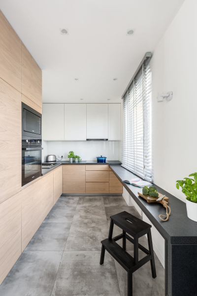 U kuchyně podlouhlého tvaru museli architekti poněkud přehodnotit její uspořádání.Vestavěné skříně jsou na dvou stěnách.Pod oknem byla instalována pracovní deska jako rozšíření parapetu.Na opačné straně je jídelna pro každodenní účely.