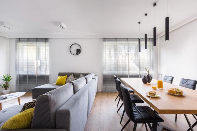 Obývací prostor je rozdělený do dvou zón: jídelna s velkým stolem a posezení s pohodlnou pohovkou.