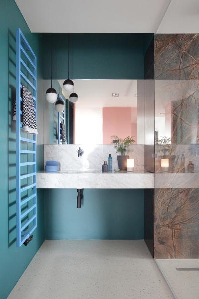 Použitím dvou výrazných barev – smaragdově zelené a růžové v kombinaci přírodních materiálů - kamene a dřeva – se docílilo rozzáření interiéru a zvýraznění jeho odlišné funkční části.