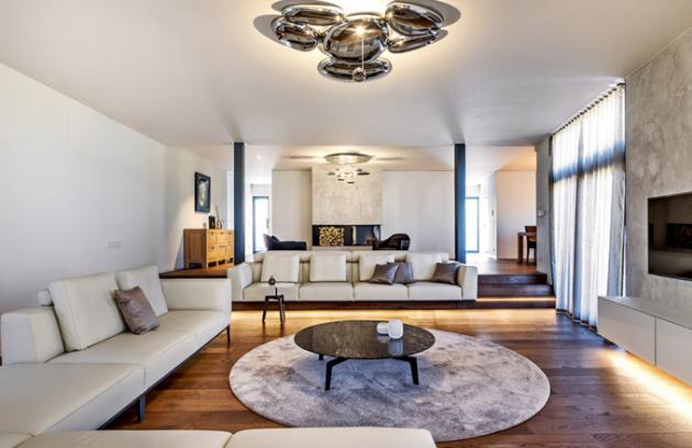 Hlavní sezení vobývací zóně je usazeno dozáměrně vytvořeného schodu vevýškovém rozdílu, který vizuálně vytváří nenásilný předěl mezi kuchyňskou oobývací zónou. Pohovka byla vyrobena namíru odvýrobce Nábytek Duchoň