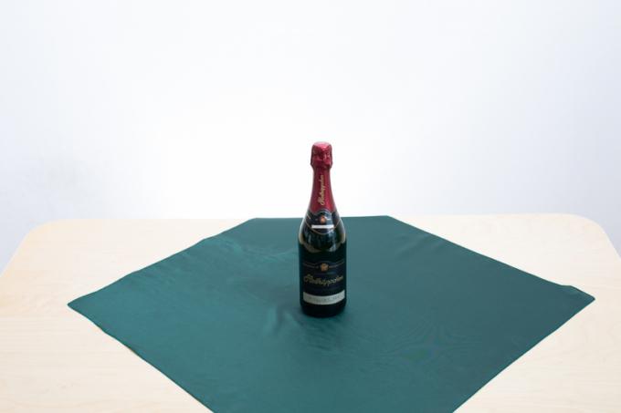 1.Položte látku na stůl a umístěte láhev do středu.