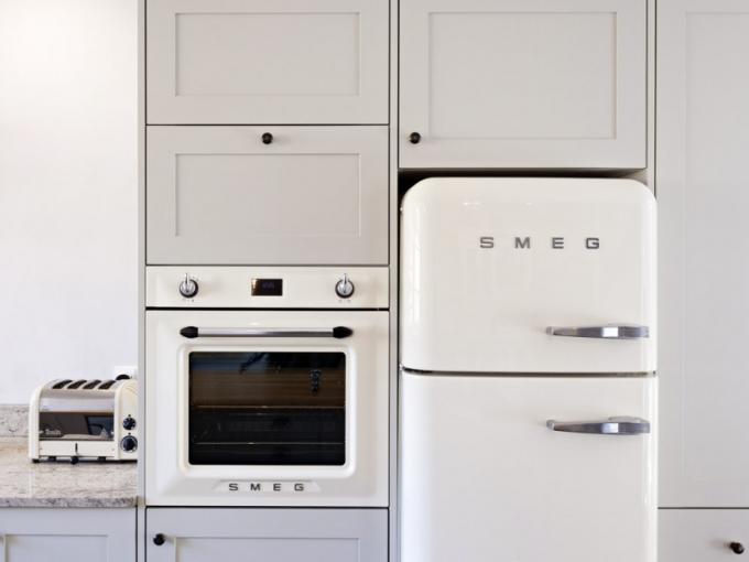 Tradiční styl abarevné ladění kuchyně vhodně doplňuje vestavná trouba achladnička Smeg zdesignové řady 50's Retro Style
