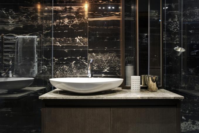 S ohledem na velikost bytu bylo nutné sloučit šatnu s koupelnou do jedné místnosti, kde opět převažují geometrické tvary a grafické prvky.
