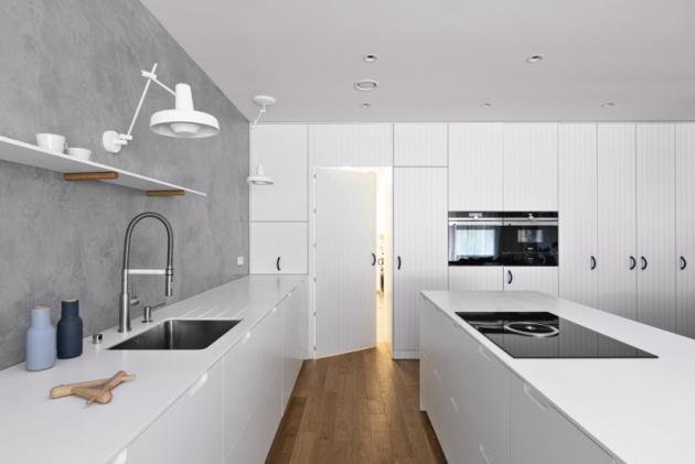 Kuchyně avelké části úložných prostor jsou navrženy vbílé barvě tak, aby neubíraly světlo anechaly vyznít struktuře dřevěné podlahy
