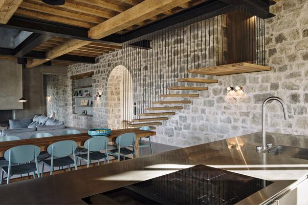 Vstupní prostor atechnická místnost jsou orientovány vzadní části domu, která je odté obytné oddělena kamennou zdí